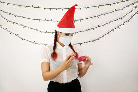 Girl in a red christmas hat and red hair, with a mask on her face opening a small red gift box and looking into it. Beautiful girl Stock Photo