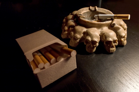 Smoking kills, sculls ashtray, pack of cigarettes Stock Photo
