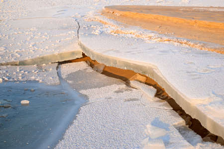 ice sheet: cracked ice sheet at the sandy bank of the river Stock Photo