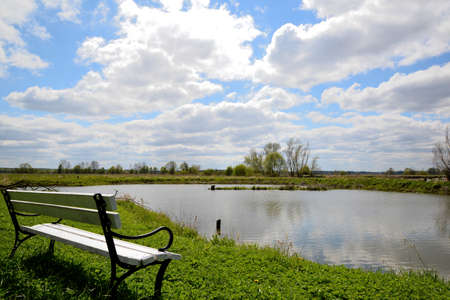 White bench on the shore of the lake and blue sky