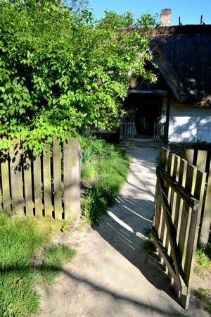 wicket door: Wide open wooden gate overlooking the garden and country house