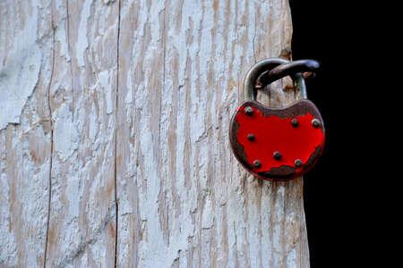 Red padlock hanging on old rural door Banco de Imagens