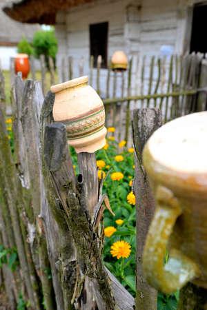 ollas de barro: Ollas de barro secado en una valla de madera rústica Foto de archivo
