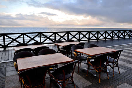 empty tables and a boulevard in the seaside resort after the season