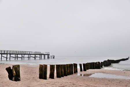 old wooden breakwater on the baltic beach after the season