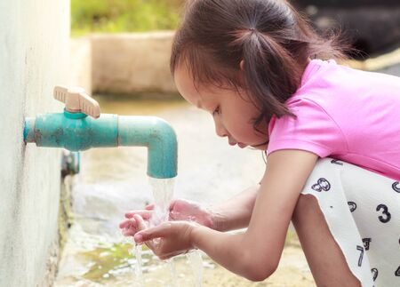 Asian child wash their hands, from PVC pipe at home.