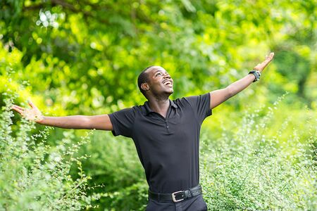 Freedom african man smiles happily in green nature. Banco de Imagens