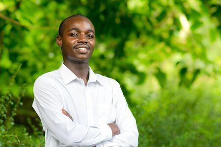 Uśmiech afrykańskiego portret mężczyzny w zielonym tle przyrody.