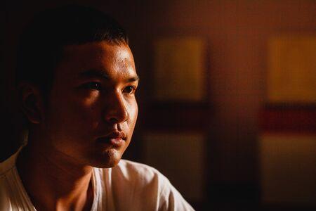 Trauriger junger Mann, der im Schlafraum denkt, zurückhaltender Stil. Standard-Bild