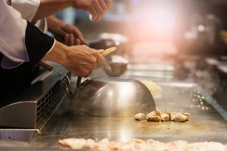 Hand of professional chef cooking pork steak on hot pan, in front of Customer