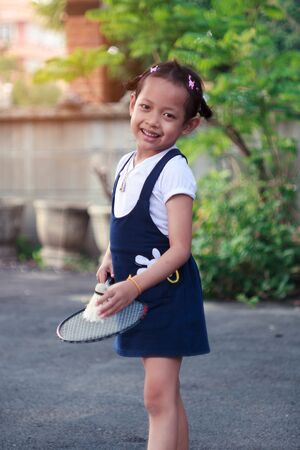 smile little girl playing badminton at home.