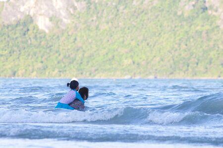 Granddaughter embraces or hug grandmother in the sea. Stok Fotoğraf
