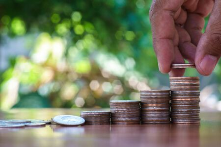Saving money concept by hand holding money coin stack growing business with bokeh of green nature.