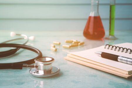 Doctor tools for good healthy with stethoscope , notebook , pen , medicine and test tube.