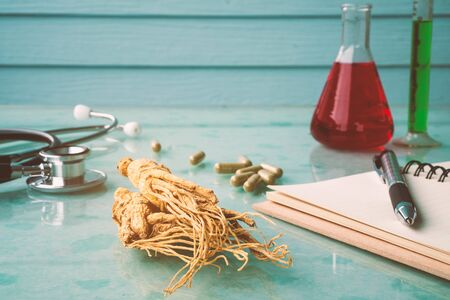 Research of ginseng for good healthy with stethoscope , notebook , pen and test tube. Stock Photo - 124953110