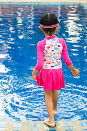 Child girl afraid to swimming in the pool and test by foots.