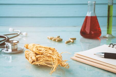 Research of ginseng for good healthy with stethoscope , notebook , pen and test tube. Banco de Imagens