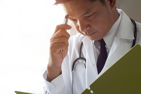 The doctor thinks and stresses when reading patient records.