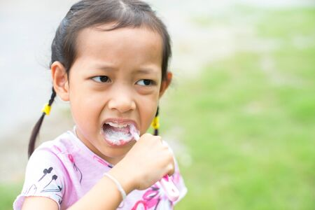 Asia child girl brush their teeth with unhappy.