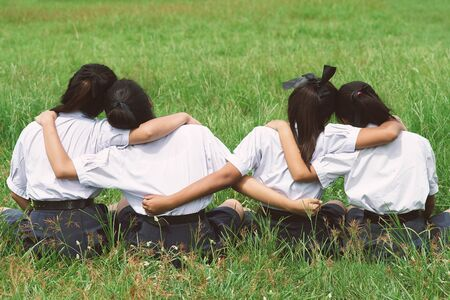 Four students girl is hugging in the field,Concept of best friends. Stock Photo