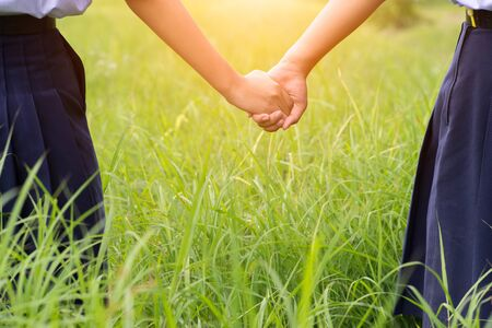 Student hold ones hands in the green field,Concept of best friends. Stock Photo