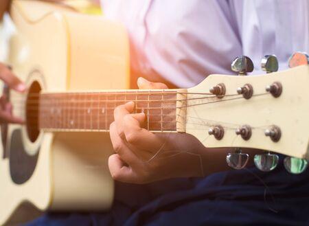 Hand of girl student playing guitar.