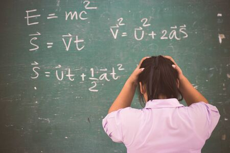 Serious girl student about  physics formula in classroom.