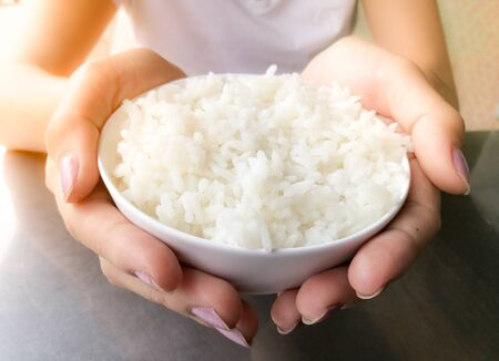 Hand of woman holding a white rice in the bowl. Imagens