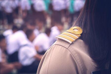 Asian thai teachers in official uniform focus on golden stripe shoulder accessory with uniform students