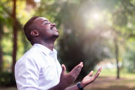 African man praying for thank god with light flare in the green nature Фото со стока