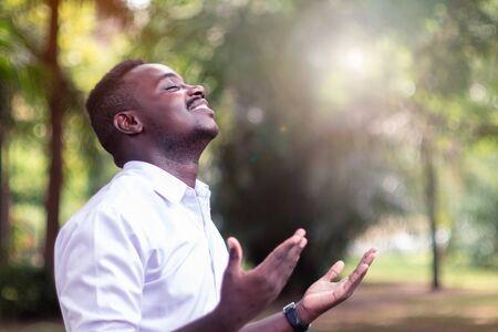 Hombre africano orando por agradecer a Dios con un destello de luz en la naturaleza verde Foto de archivo
