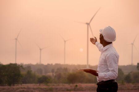 Afrikanischer Ingenieur mit weißem Schutzhelm, der mit digitalem Tablet gegen Windkraftanlage steht Standard-Bild