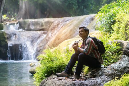 Traveler man with backpack holding camera with green natural background.