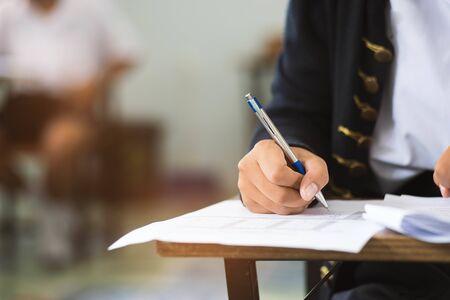 Gros plan Étudiants écrivant et lisant des exercices de feuilles de réponses aux examens en classe de l'école avec stress. Banque d'images