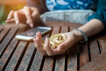 woman s hand holding gold coin of bitcoin and use smartphone.