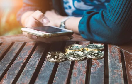 woman 's hand holding gold coin of bitcoin and use smartphone. Stock fotó