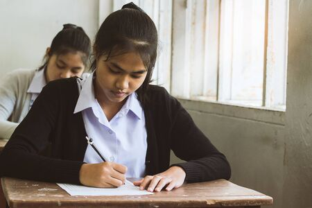 Students writing pen in hand doing exams answer sheets exercises in classroom with stress.
