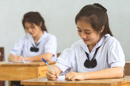 Students writing pen in hand doing exams answer sheets exercises in classroom with not stress.