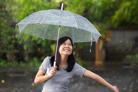 Lächeln Sie Frau im Regen mit Regenschirm Standard-Bild
