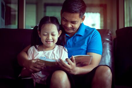 Father and his daughter reading a book at home.Vintage Style