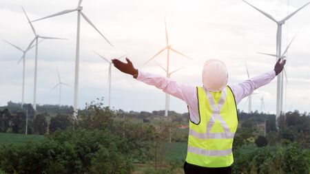 Freedom african engineer standing  with wind turbine.16:9 Style