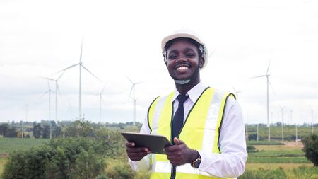 African Engineer standing and hoding laptop with wind turbine.16:9 style
