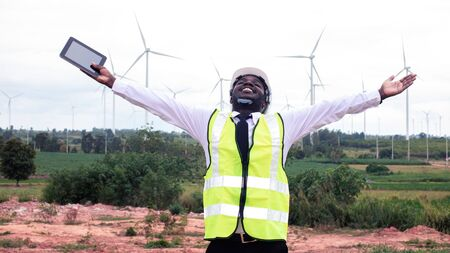 Freedom african engineer standing and hoding laptop with wind turbine.16:9 style Banco de Imagens