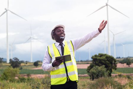 African engineer standing and hoding laptop with wind turbine. Banco de Imagens