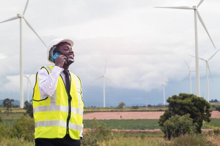 African engineer standing and talking smartphone with wind turbine