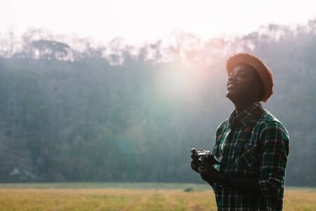 African man traveler holding film camera with a green meadow and mountain
