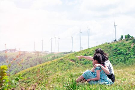 Happy asian family mother and daughter sitting on top of beautiful mountain with the turbine in background Foto de archivo - 132051475