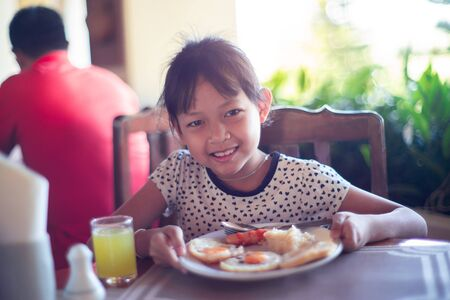 Smile asian child girl eating breakfast in a restaurant