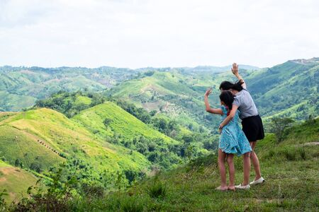 Happy asian family mother and daughter standing on top of beautiful mountain holding raised hands Imagens
