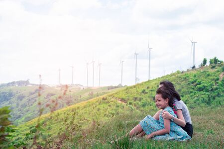 Happy asian family mother and daughter sitting on top of beautiful mountain with the turbine in background